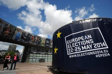 People walk in front of visuals promoting the vote for the European elections in front of the European Parliament in Brussels