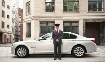 Un chofer de pie junto a un BMW en Londres, donde uno de cada 45 habitantes es un millonario, las cifras muestran. Fotografía: Cultura Creativa / Alamy