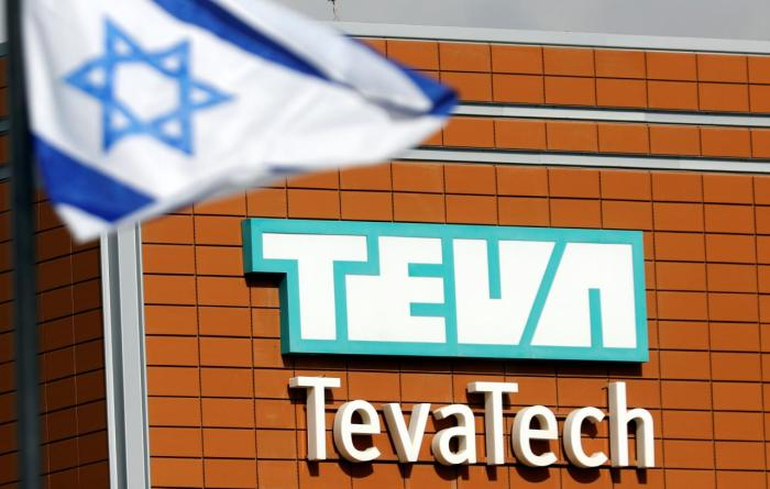 An Israeli flag flutters near the logo of Teva Tech which is part of Teva Pharmaceutical Industries in Neot Hovav, southern Israel