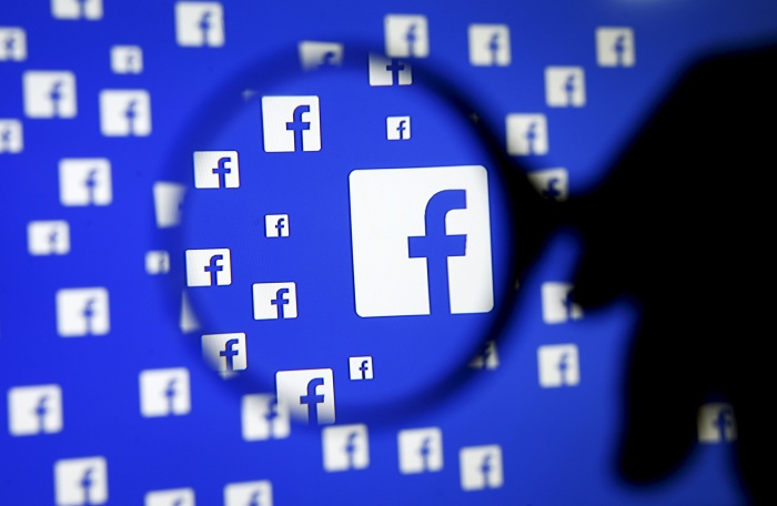 A man poses with a magnifier in front of a Facebook logo on display in this illustration taken in Sarajevo